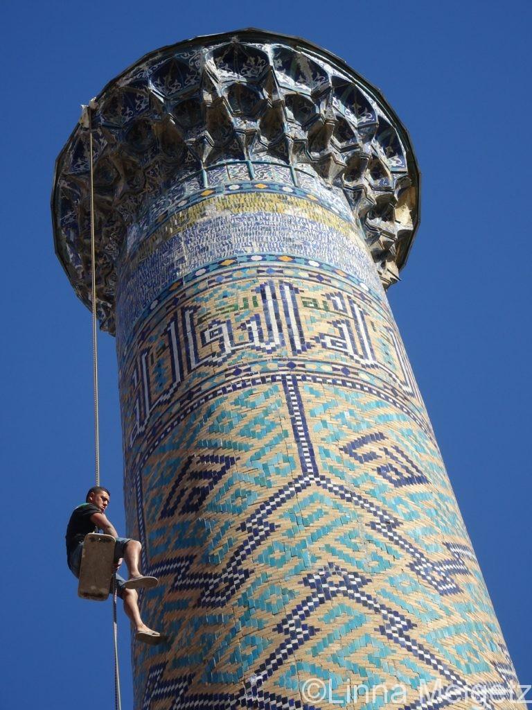 シェルダル・マドラサのミナレットに男性が登っている