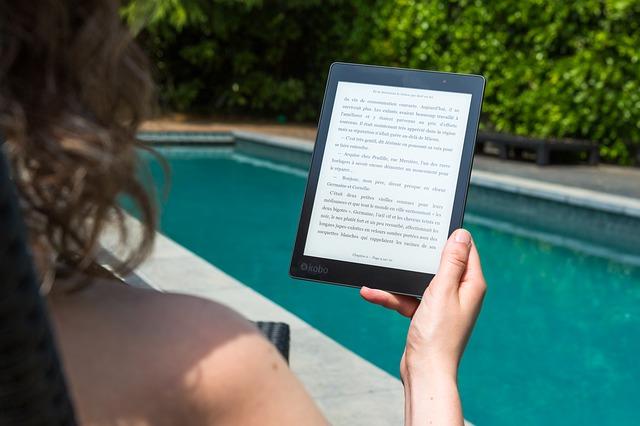 プールサイドでスマホ上で英語を読んでいる女性の写真