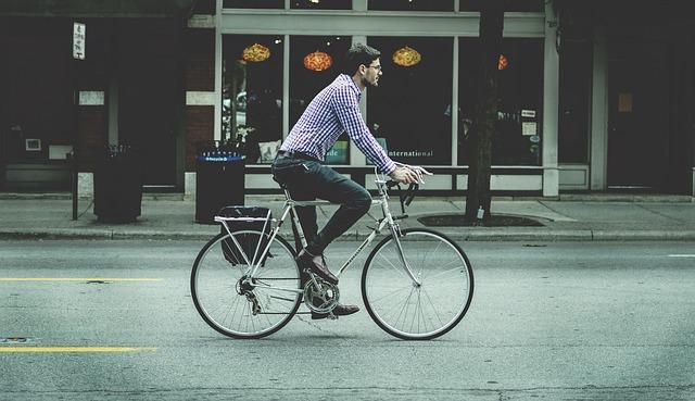 自転車に乗ってどこかへ行く人の写真