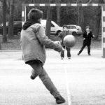 公園でサッカーをする子どもたちの写真